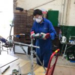 Hazel on the angle-grinder cutting tube lengths