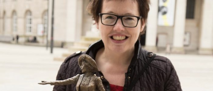 Hazel Reeves posing with the small Our Emmeline statue
