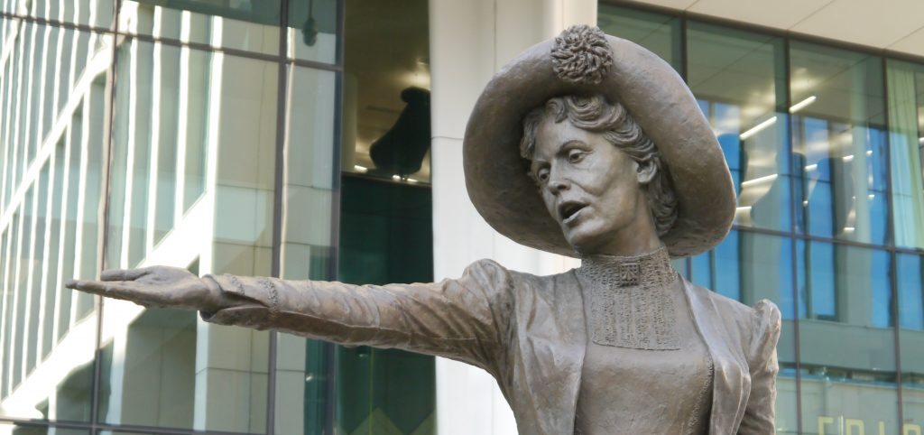 Photo show image of the Emmeline Pankhurst statue, with her arm oustretched to urge women to demand the vote